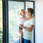 Cheerful father holding cute daughter, looking at her and smiling. Lovely blonde girl looking at camera. Happy dad with kid standing near balcony open door. Relocation and family moving day concept